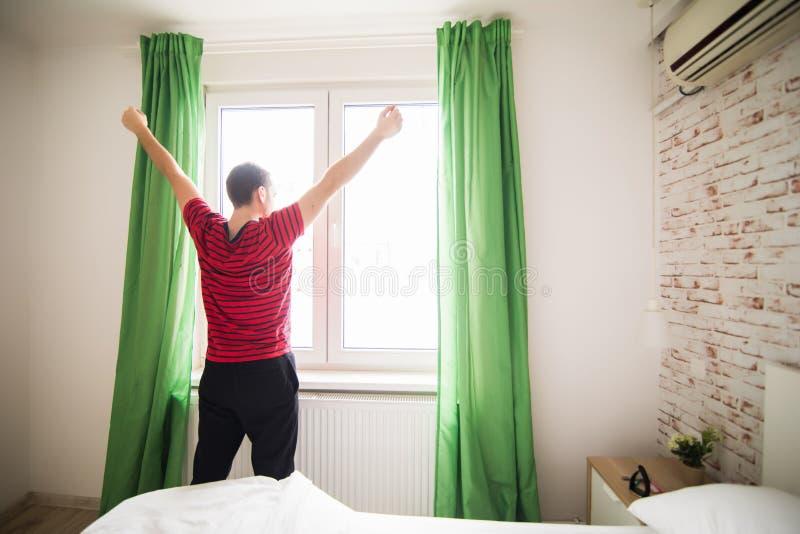 O homem considerável que acorda nas mãos de aumentação da cama à janela na manhã com sentimento fresco relaxa imagens de stock