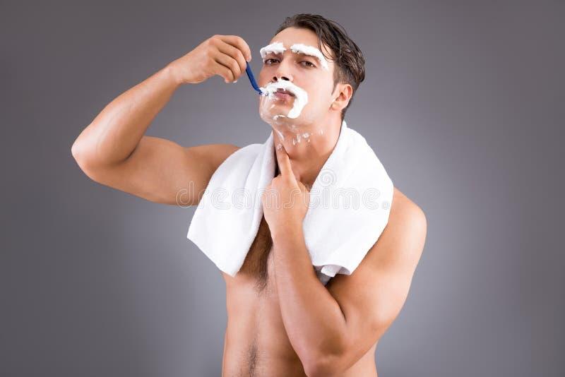 O homem considerável que barbeia contra o fundo escuro fotografia de stock royalty free