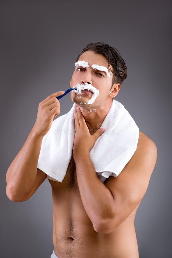 O homem considerável que barbeia contra o fundo escuro fotos de stock royalty free