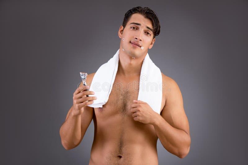 O homem considerável que barbeia contra o fundo escuro foto de stock