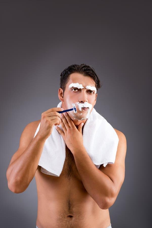 O homem considerável que barbeia contra o fundo escuro imagens de stock royalty free