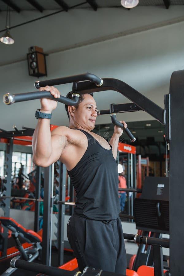 O homem considerável que exercita e que faz a tração levanta foto de stock