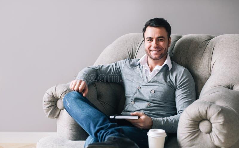 O homem considerável que senta-se em uma poltrona olha afastado foto de stock