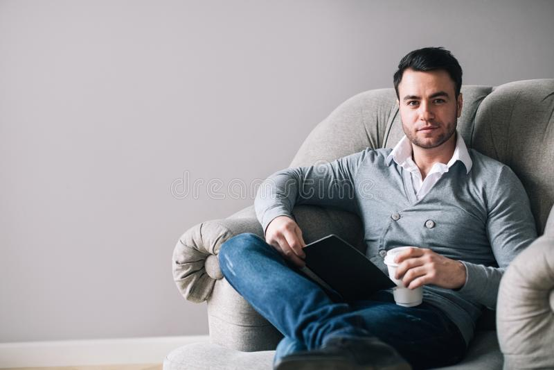 O homem considerável que senta-se em uma poltrona olha afastado imagem de stock
