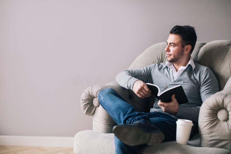 O homem considerável que senta-se em uma poltrona olha afastado fotografia de stock