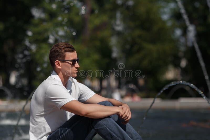 O homem considerável que senta-se nos óculos de sol aproxima a fonte fotografia de stock royalty free