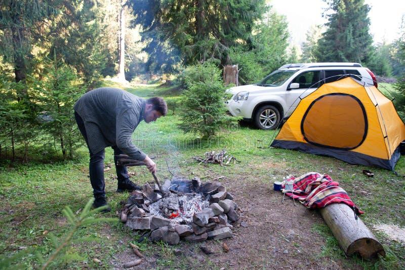 O homem constrói o fogo na floresta, carro com a barraca amarela no fundo fotografia de stock royalty free