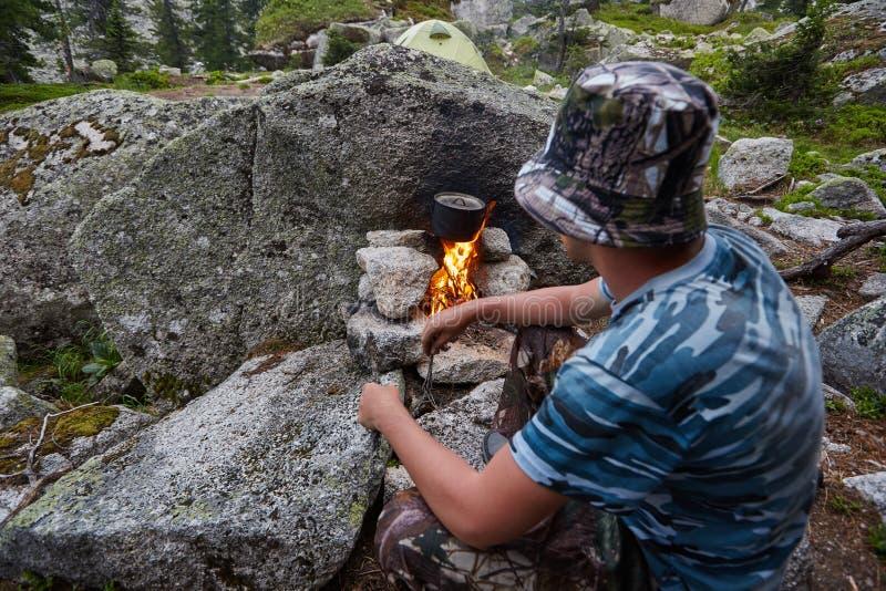 O homem construiu uma fogueira nas madeiras na natureza Sobreviva nas montanhas na floresta, cozinhando em uma bandeja do potenci imagens de stock