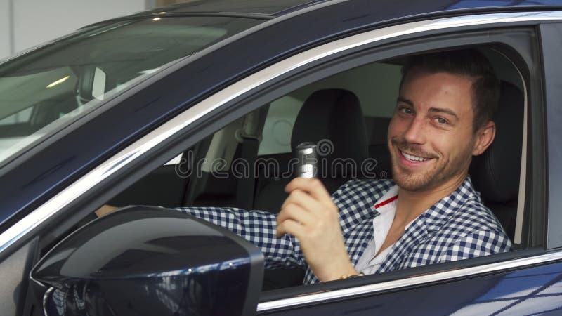 O homem contínuo senta-se em seu carro novo foto de stock royalty free