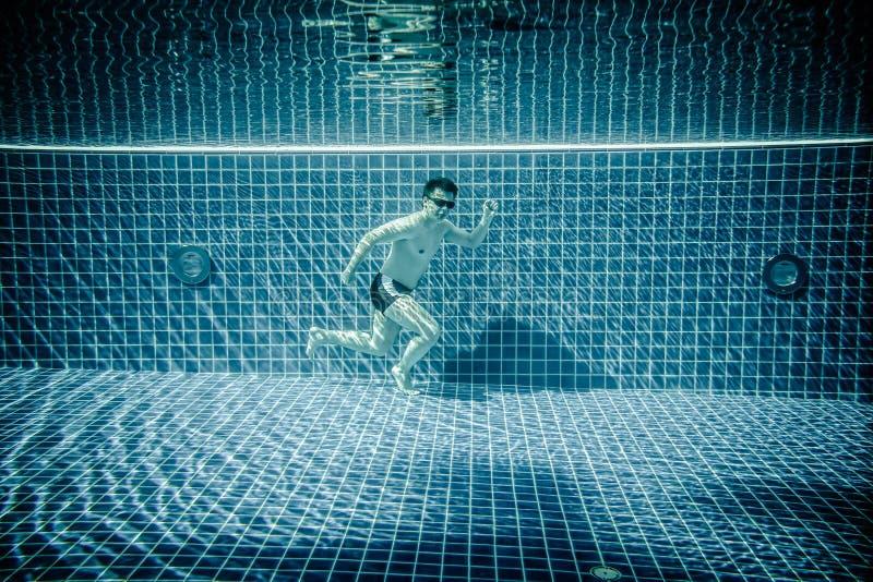 O homem corre a piscina subaquática imagens de stock royalty free