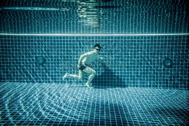 O homem corre a piscina subaquática foto de stock royalty free