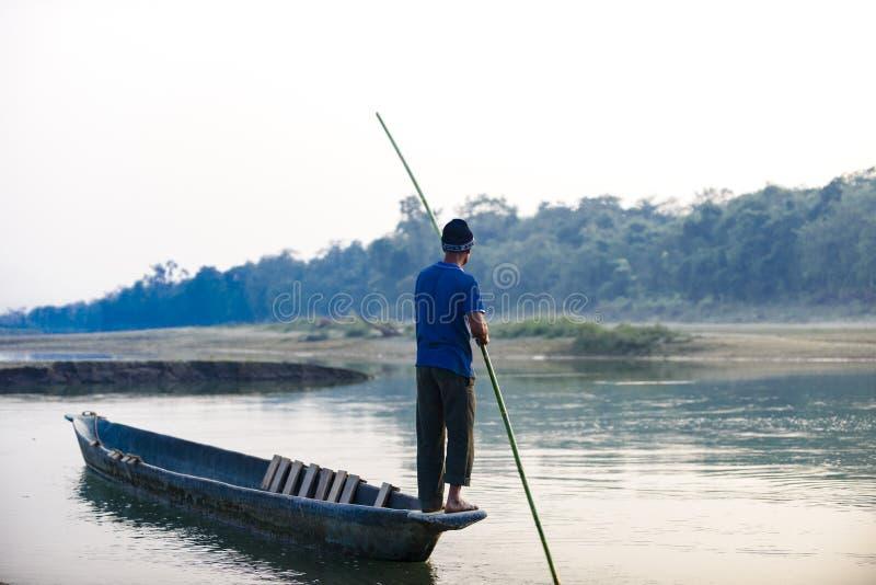 O homem corre um barco de madeira no rio, Nepal, parque nacional de Chitwan, fotografia de stock