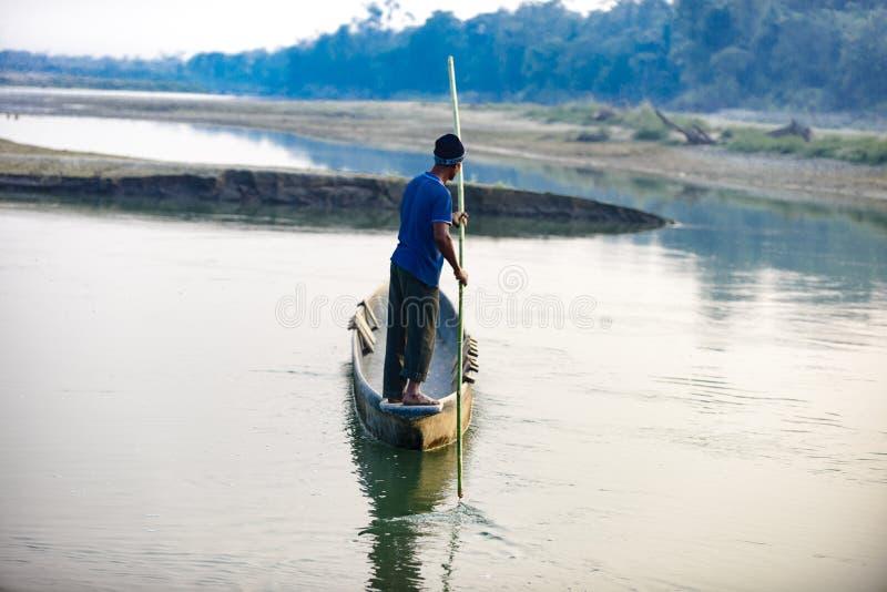 O homem corre um barco de madeira no rio, Nepal, parque nacional de Chitwan, imagem de stock