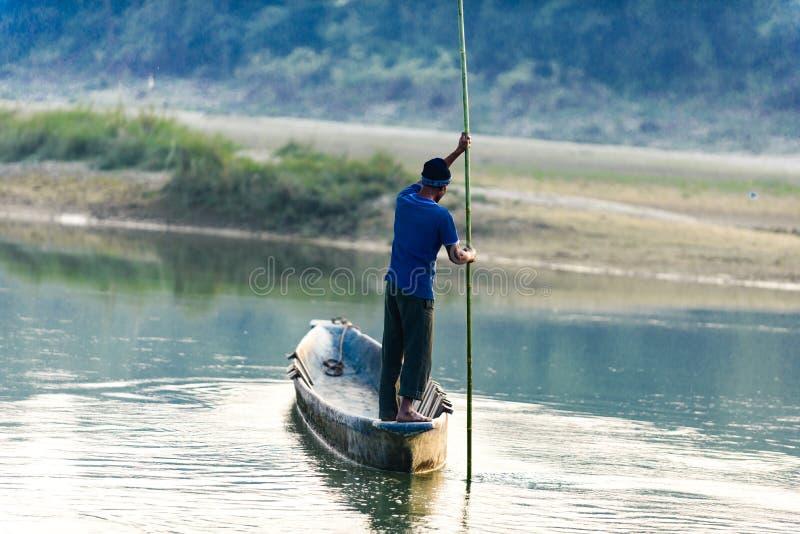O homem corre um barco de madeira no rio, Nepal, parque nacional de Chitwan, fotografia de stock royalty free