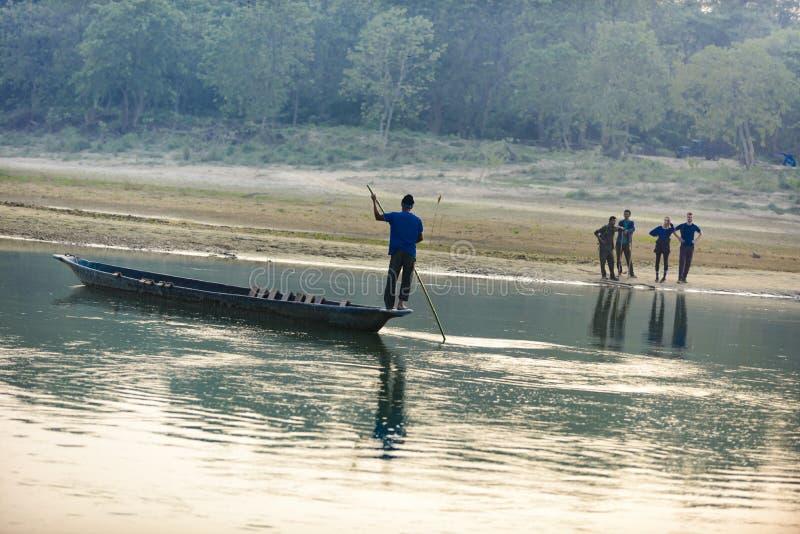 O homem corre um barco de madeira no rio, Nepal, parque nacional de Chitwan, fotos de stock