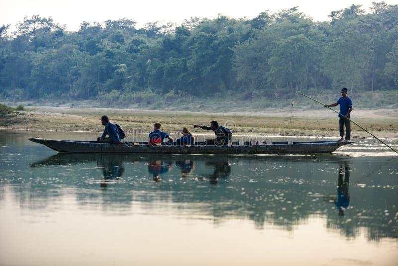 O homem corre um barco de madeira no rio, Nepal, parque nacional de Chitwan, foto de stock