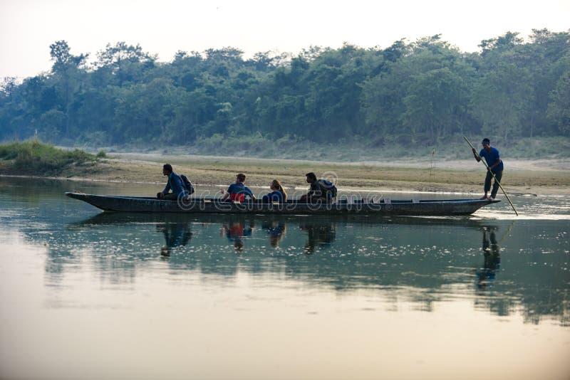 O homem corre um barco de madeira no rio, Nepal, parque nacional de Chitwan, imagens de stock royalty free