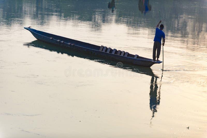 O homem corre um barco de madeira no rio, Nepal, parque nacional de Chitwan, imagem de stock royalty free