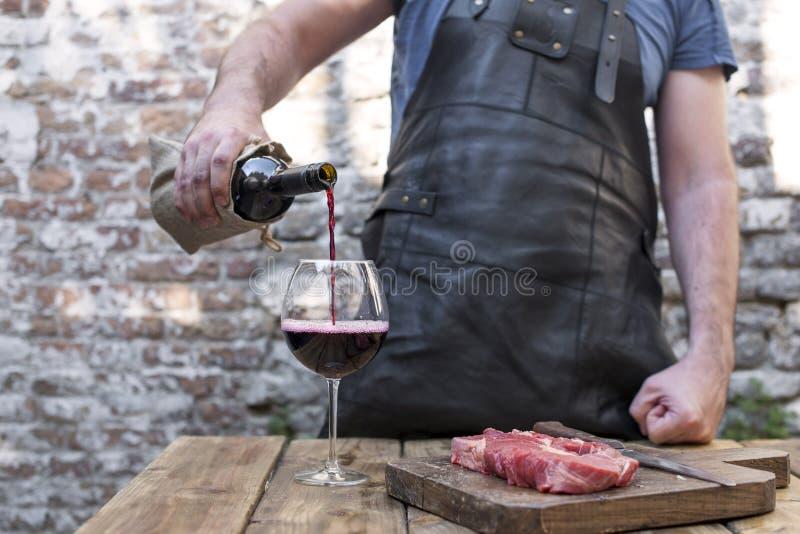 O homem corta a carne para o jantar e derrama um vidro do vinho tinto da garrafa Um partido com alimento e álcool Copie o espaço fotografia de stock royalty free