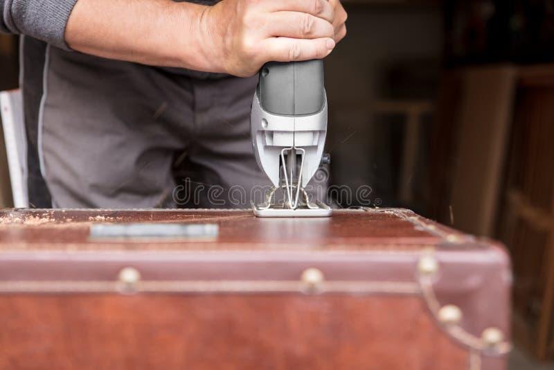 O homem corta um entalhe em uma caixa foto de stock