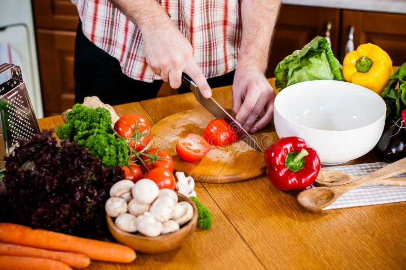 O homem corta vegetais frescos da mola fotos de stock