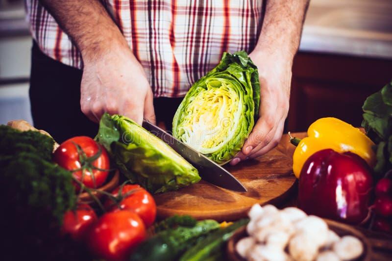 O homem corta vegetais frescos da mola fotos de stock royalty free