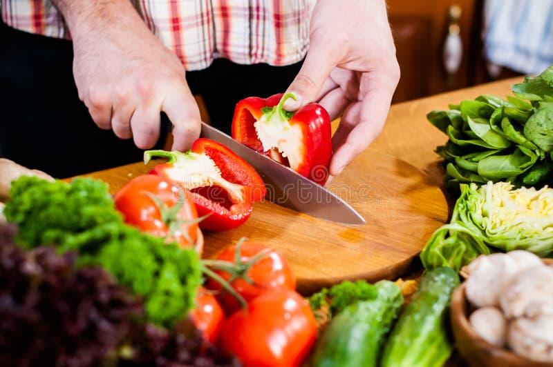 O homem corta vegetais frescos da mola foto de stock
