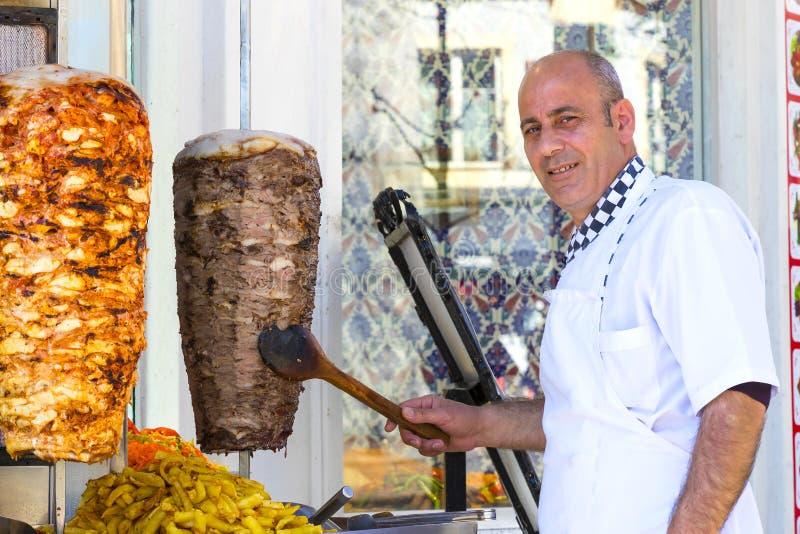 O homem cozinha o no espeto turco da carne em um café da rua fotos de stock