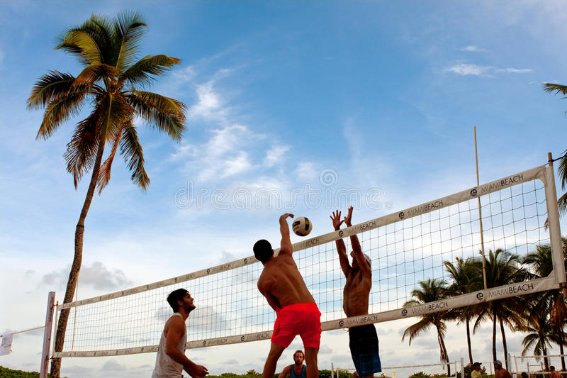 O homem crava a bola após o construtor no jogo de voleibol de Miami Beach imagem de stock royalty free