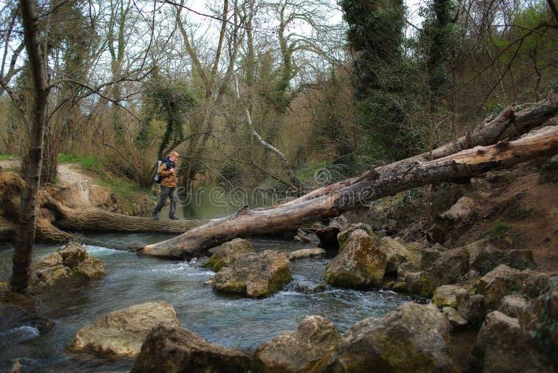 O homem cruza um rio ao longo de um log da árvore imagens de stock royalty free