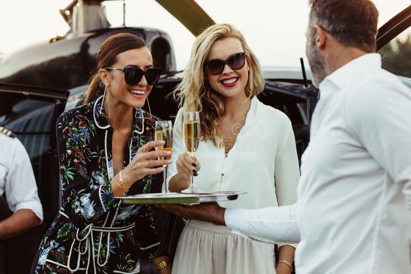 O homem cumprimenta amigos fêmeas com vinho imagem de stock