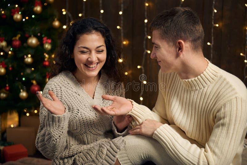 O homem dá à menina um anel de noivado, par está nas luzes e na decoração de Natal, vestidas em branco, árvore de abeto em de mad imagem de stock royalty free