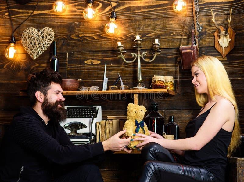 O homem dá ao urso de peluche da senhora como o presente no aniversário Conceito do aniversário Os pares no amor nas caras de sor foto de stock
