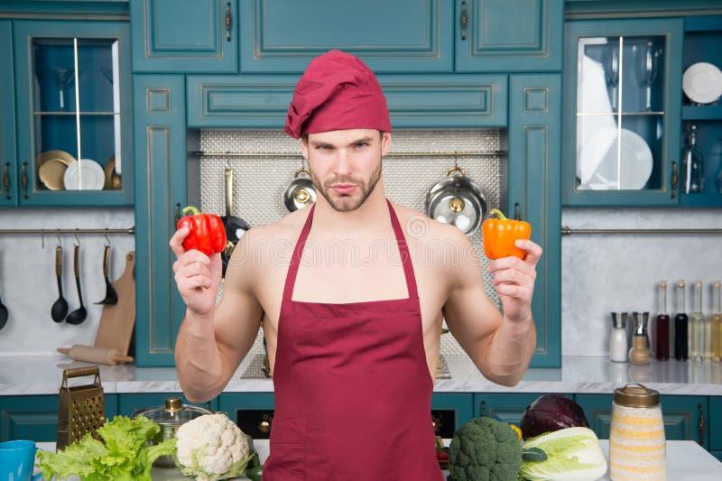 O homem dá a classe mestra no cozimento Cozinheiro mestre pronto para o cozimento alto da classe Pimentas da posse do cozinheiro  foto de stock royalty free