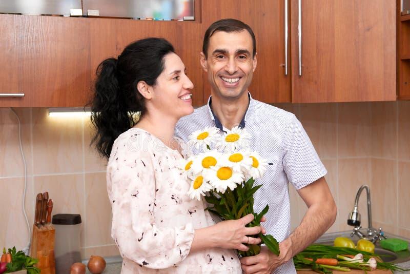 O homem dá flores da camomila à mulher gravida, par no interior com frutas e legumes frescas, conceito saudável da cozinha do ali fotos de stock royalty free