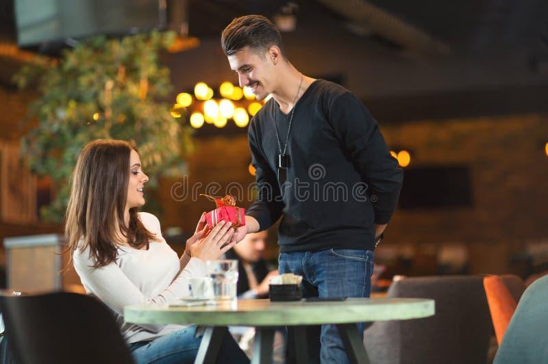 O homem dá um presente a uma moça no café fotografia de stock