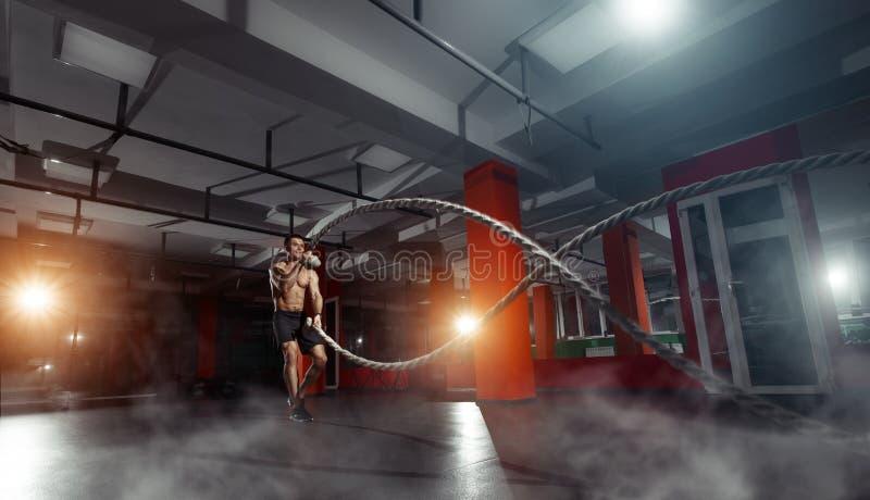 O homem da aptidão que dá certo com batalha ropes em um gym fotos de stock royalty free