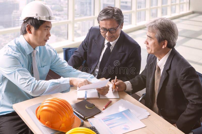 O homem da engenharia e a equipe superior da arquitetura projetam a reunião dentro fotografia de stock