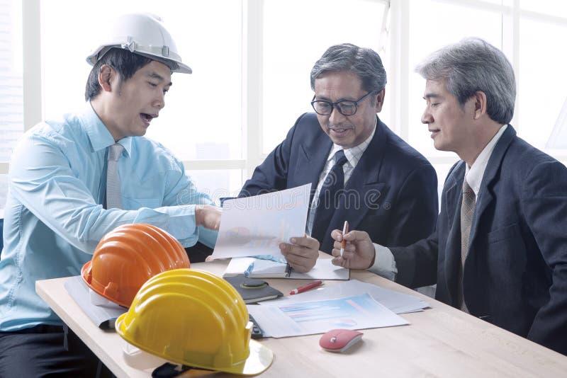 O homem da engenharia e a equipe superior da arquitetura projetam a reunião dentro imagens de stock royalty free