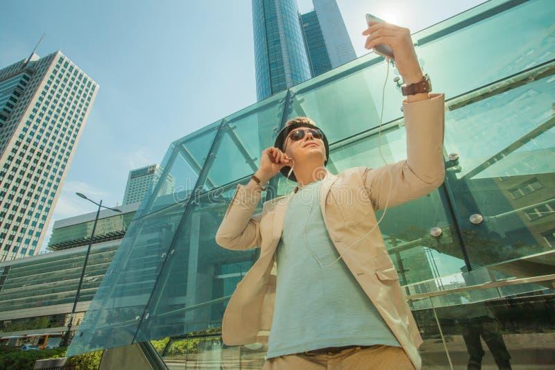 O homem da forma faz o selfie na cidade grande na perspectiva dos arranha-céus Conceito do estilo do curso e de vida fotografia de stock