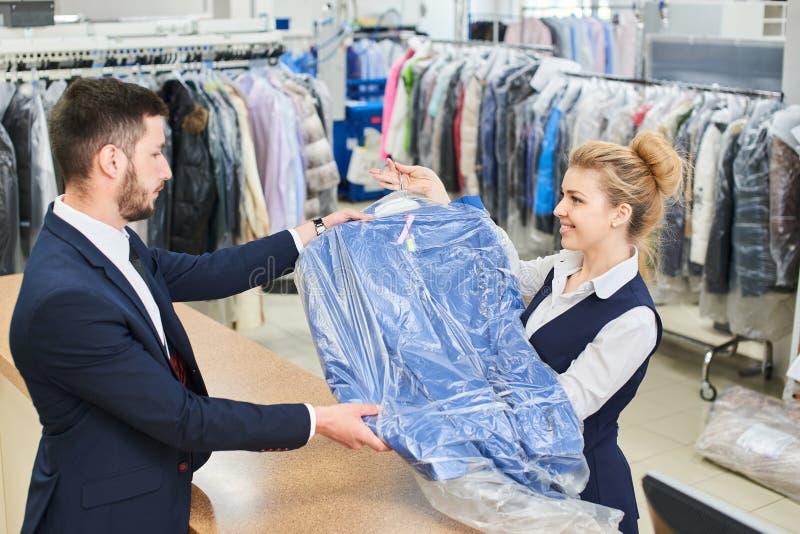 O homem da lavanderia do trabalhador da menina dá ao cliente a roupa limpa fotografia de stock royalty free