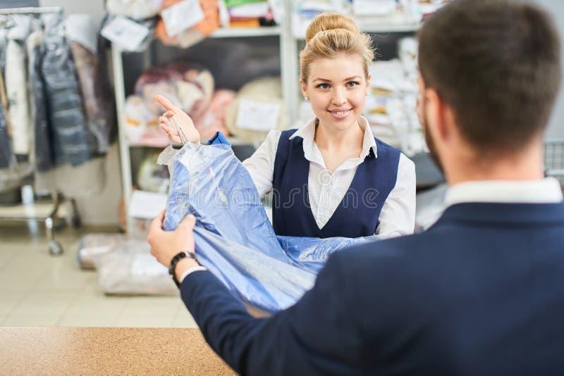 O homem da lavanderia do trabalhador da menina dá ao cliente a roupa limpa nos líquidos de limpeza secos imagem de stock royalty free