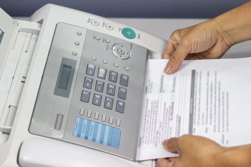 O homem da mão está usando um fax no escritório foto de stock