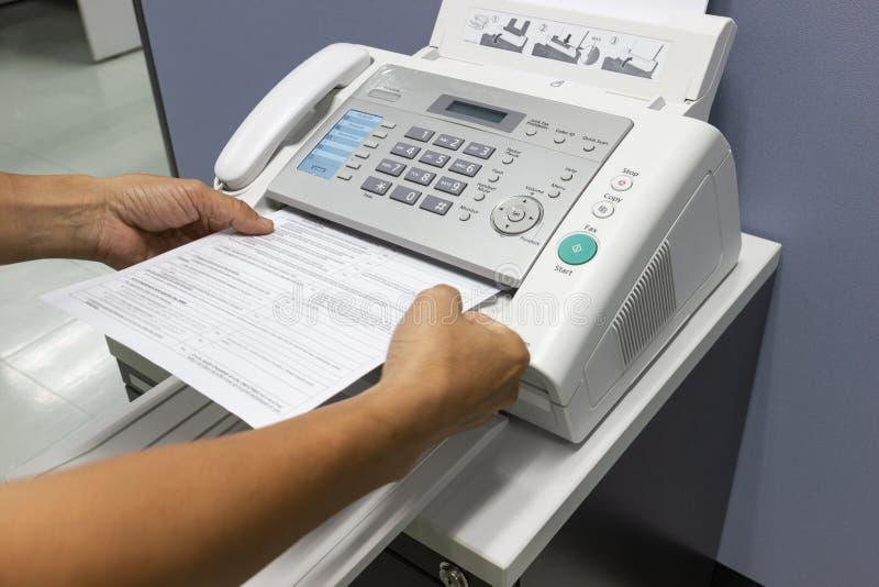 O homem da mão está usando um fax no escritório fotografia de stock
