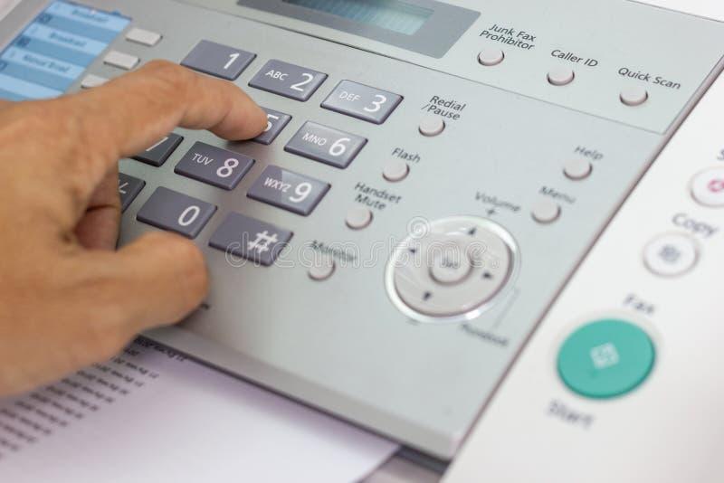 O homem da mão está usando um fax no escritório imagens de stock royalty free