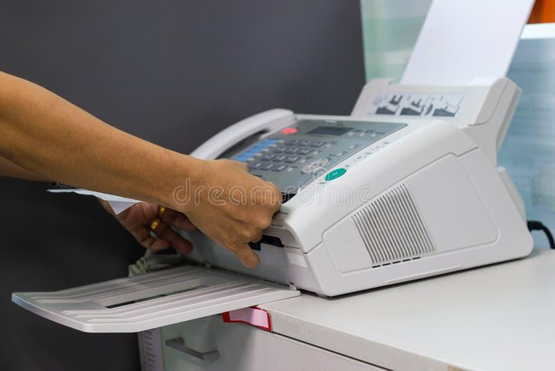 O homem da mão está usando um fax no escritório imagem de stock royalty free