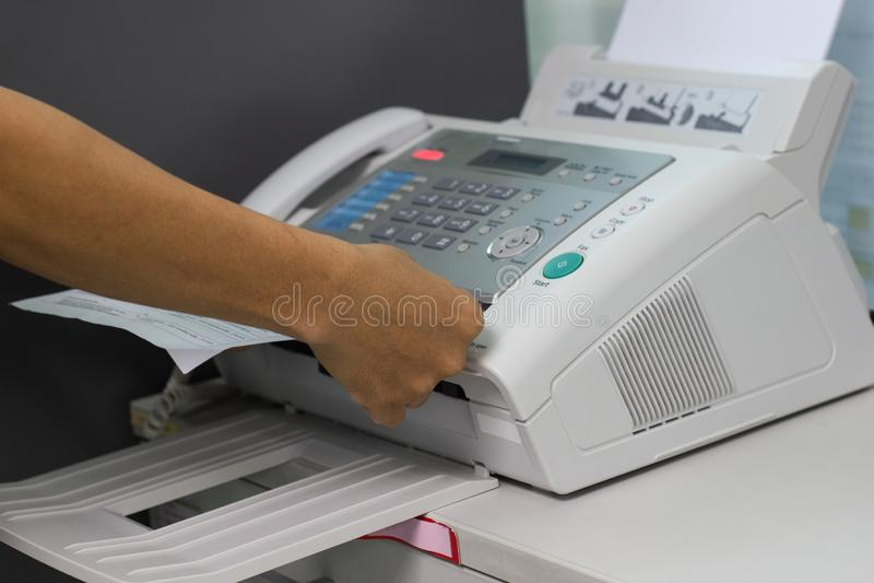 O homem da mão está usando um fax no escritório fotos de stock