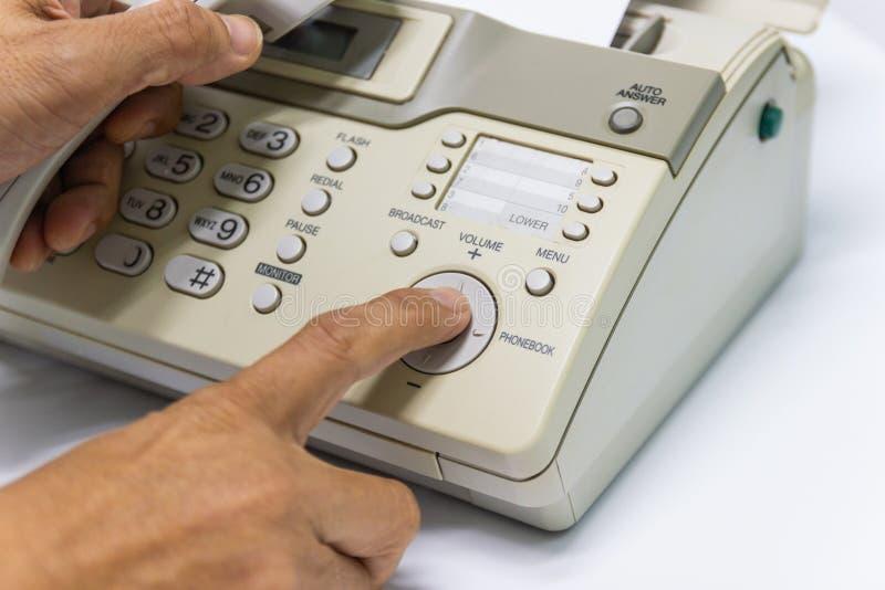 O homem da mão está usando um fax no escritório foto de stock royalty free