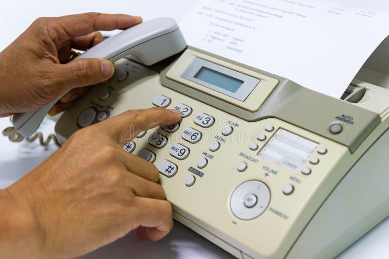 O homem da mão está usando um fax no escritório fotografia de stock royalty free
