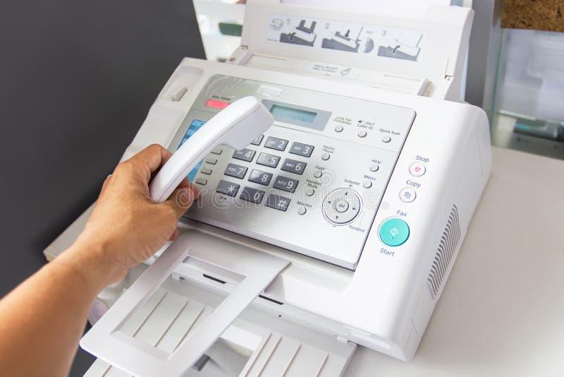 O homem da mão está usando um fax no escritório imagem de stock